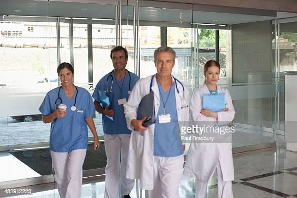 Vier hospital Arbeitnehmer zu Fuß in Gang halten clipboards und Lächeln