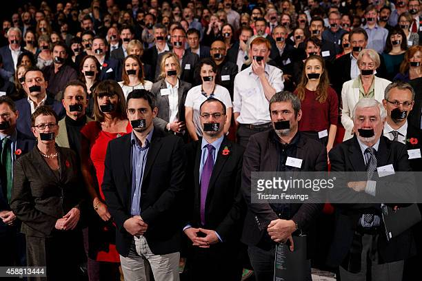 Four hundred journalists and Amnesty International supporters tape their mouths closed to show solidarity with Al Jazeera journalists jailed in Egypt...