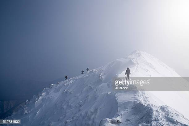 Four ice climbers scaling a mountains summit