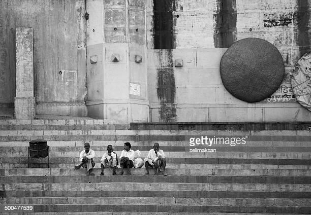 Four Indian men sitting on steps of Ghats in Varanasi