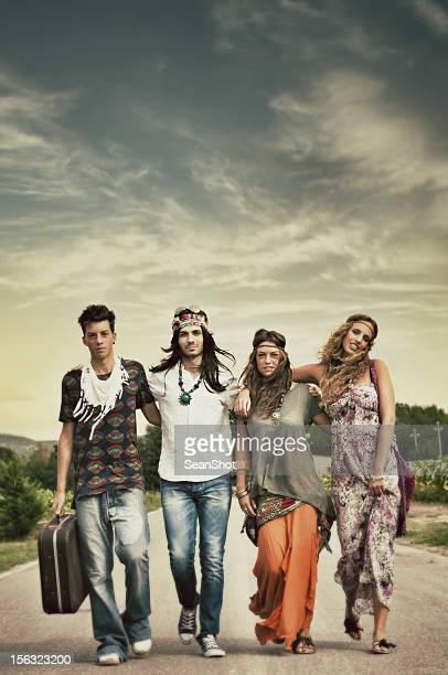 Four individuals walking on the road in hippie-style clothes