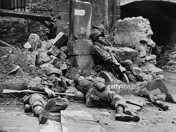 Four infantrymen of the 20th 'Yankee' Div 3rd US Army catch a few moments of rest in the debrislittered street of Fulda April 3 1945