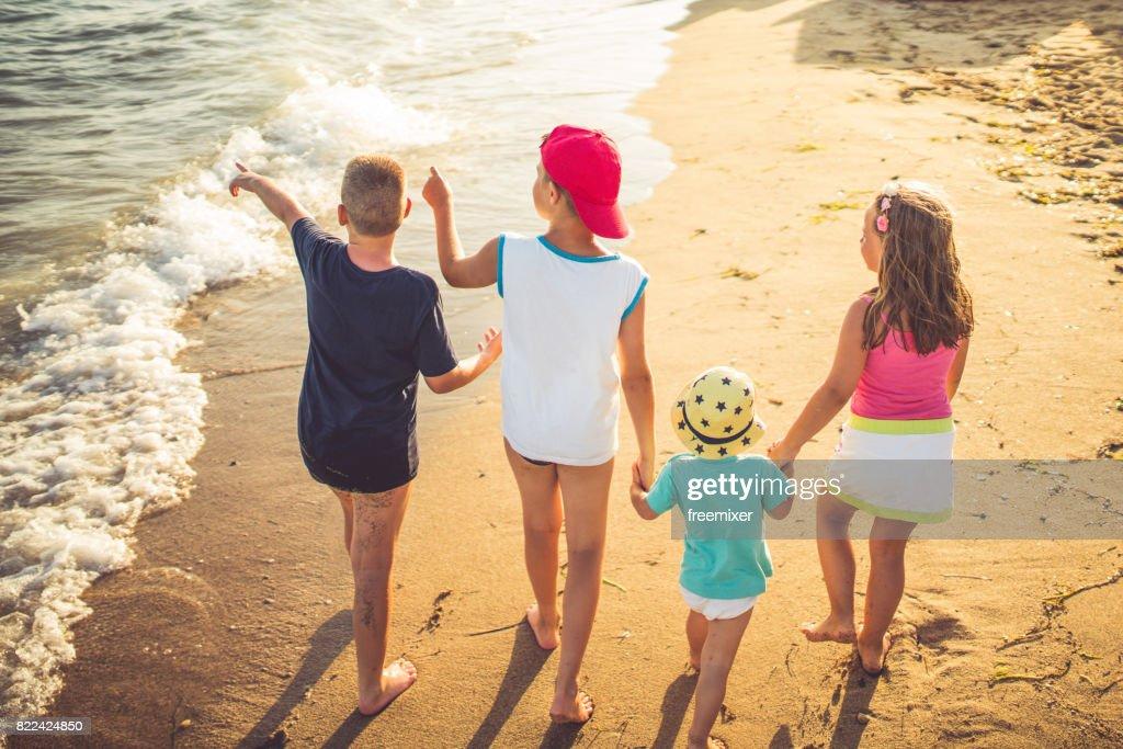 Four kids having fun on the beach : Stock Photo
