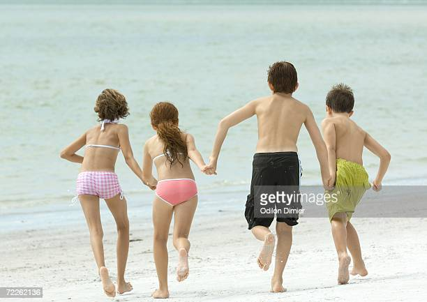 Four kids holding hands and running toward water, on beach, rear view
