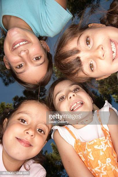 four kids (5-9) in huddle outdoors, portrait, view from below - only girls stock pictures, royalty-free photos & images