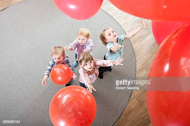 Four kids playing with red balloons in kindergarten, elevated view