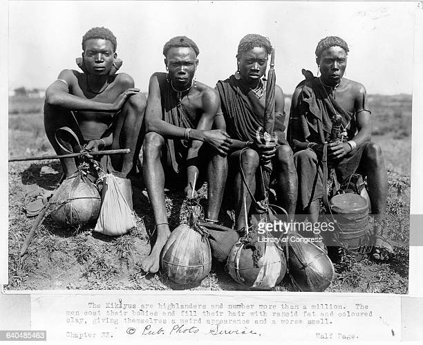 Four Kikuyu men sit on the grass with their water gordes lying in fron tof them Africa 1920s