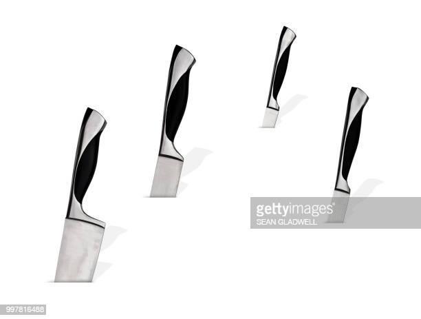 four kitchen knives sticking into white background - küchenmesser stock-fotos und bilder