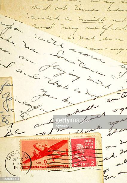 four letters and two stamps - love letter stock photos and pictures