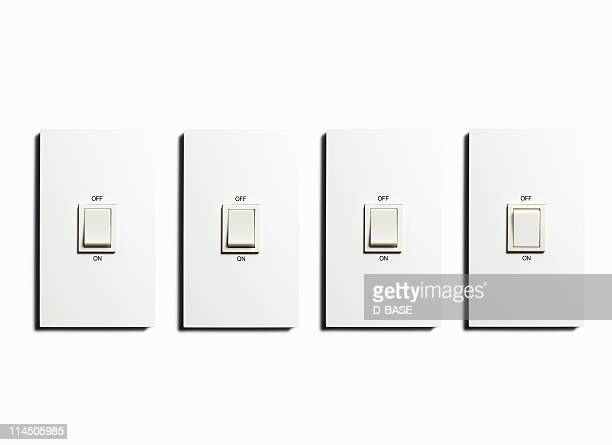 four Light switch on  the white wall