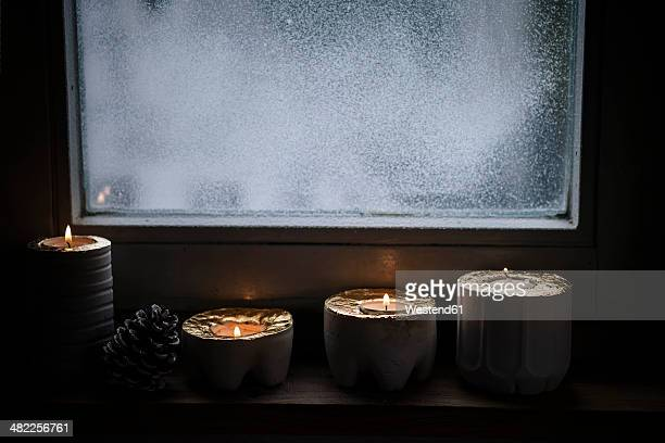 Four lighted advent candles and a fir cone in front of snow covered window