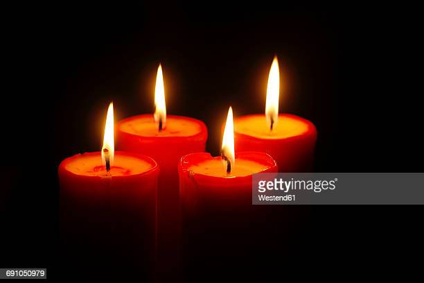 Four lighted red candles