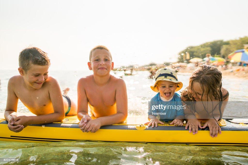 Four little surfers : Stock Photo