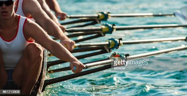 four male athletes rowing across lake in late afternoon - image focus technique stock pictures, royalty-free photos & images
