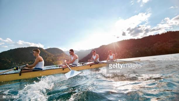 quatro atletas masculinos remo lago no fim da tarde - remando - fotografias e filmes do acervo