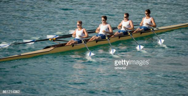 Four male athletes rowing across lake in late afternoon