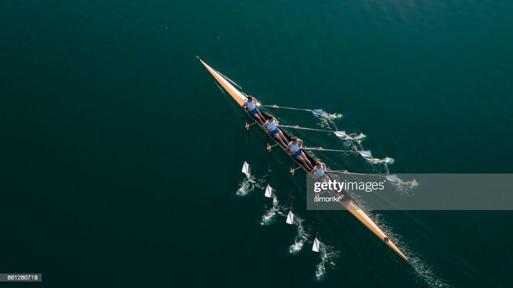 Four male athletes sculling on lake in sunshine : Stock Photo