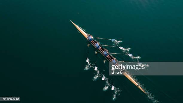 four male athletes sculling on lake in sunshine - competizione foto e immagini stock