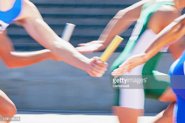 four male runners passing relay baton - relay baton stock photos and pictures