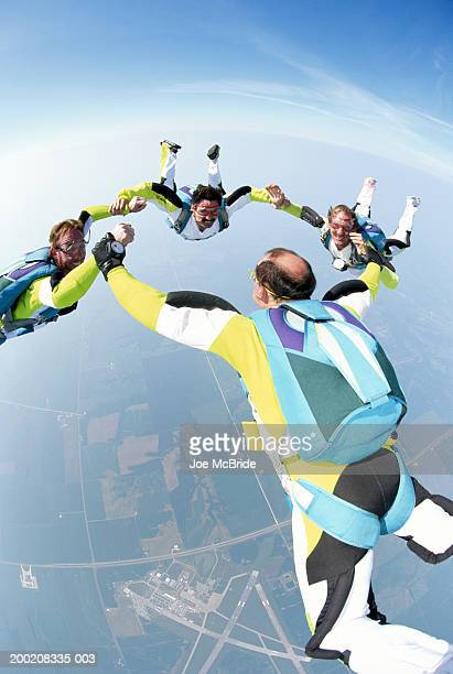 Four male skydivers in formation, holding hands, aerial view