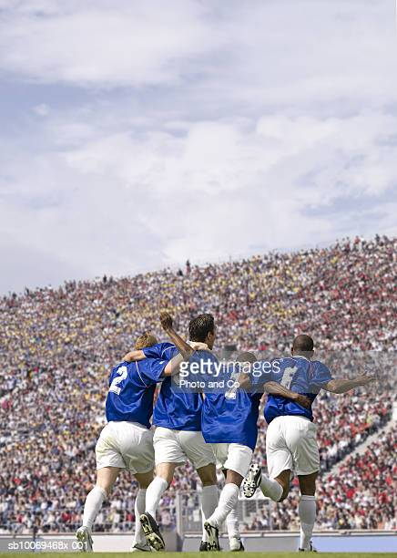 four male soccer players celebrating in stadium, rear view - french football photos et images de collection
