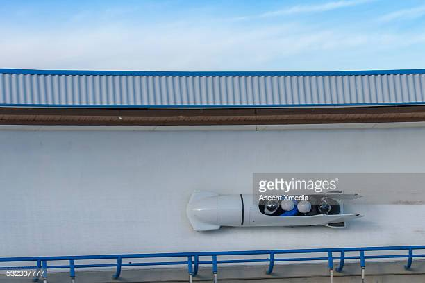 four man bobsled on track, overhead view - bobsleigh stock pictures, royalty-free photos & images