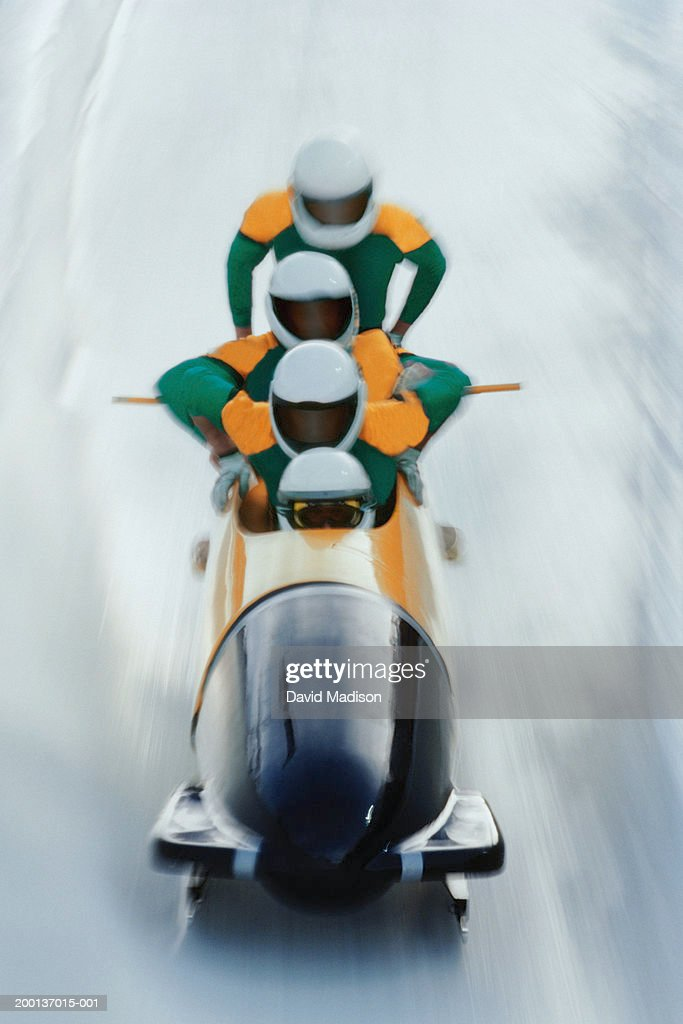 Four man bobsled team mounting their sled (blurred motion) : Stock Photo