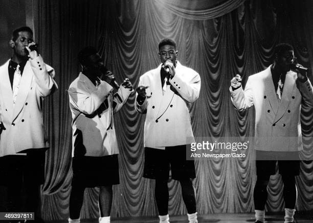 A four man singing group Boyz II Men specialists in RB soul and acapella music founded in 1988 on stage singing in white tuxedos and black shorts 1988