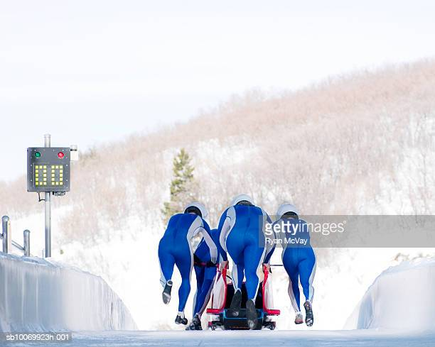 Four man team launching bob-sleigh, rear view
