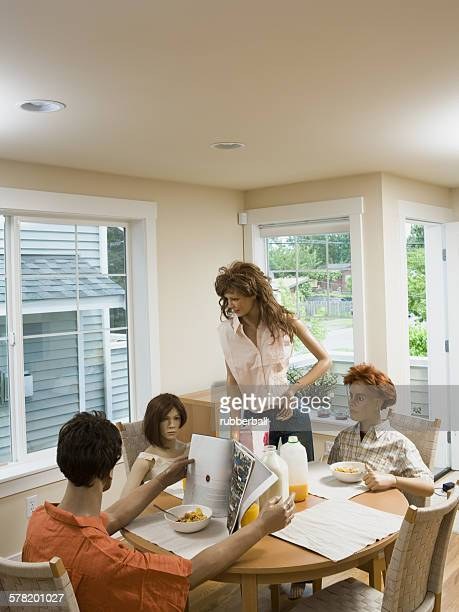 four mannequins portraying a family at the dining table - futurista ストックフォトと画像