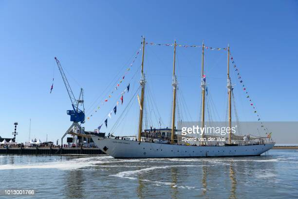Four mast lugger Santa Maria Manuela from Portugal arriving in Harlingen port where people on the quay are watching the ships arriving during the...