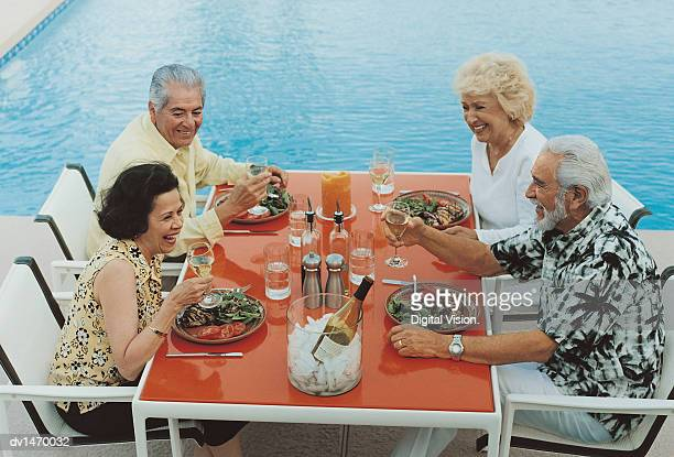 Four Mature Friends Sit Face to Face at a Table Near a Swimming Pool