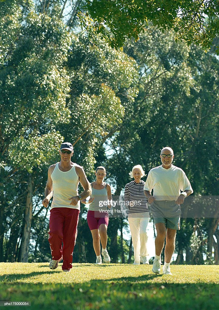 Four mature joggers in park : Stockfoto