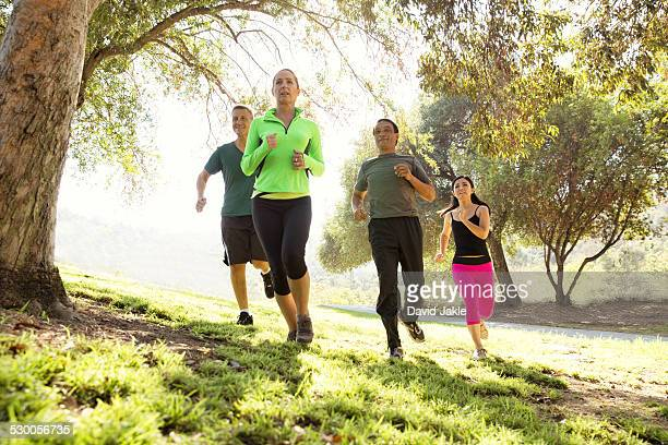 Four mature men and women running in park