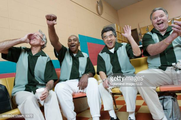 four mature men cheering in a bowling alley - short sleeved stock pictures, royalty-free photos & images
