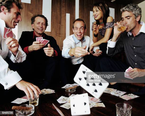 Four mature men playing cards watched by young woman