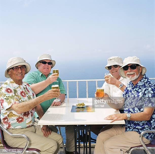 Four mature men toasting drinks at table outdoors on balcony, portrait