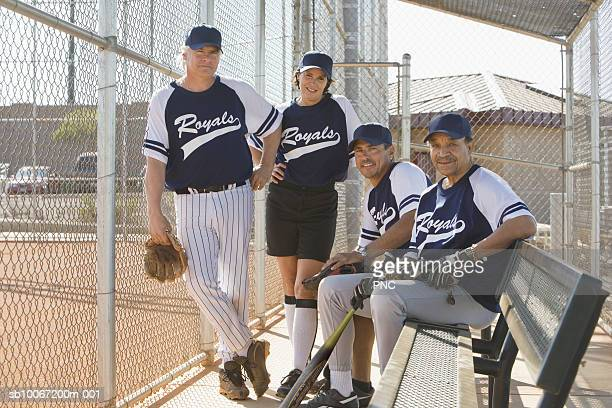 four mature softball players in dugout, portrait - softball stock pictures, royalty-free photos & images