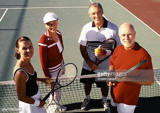 Four mature tennis players on court, portrait