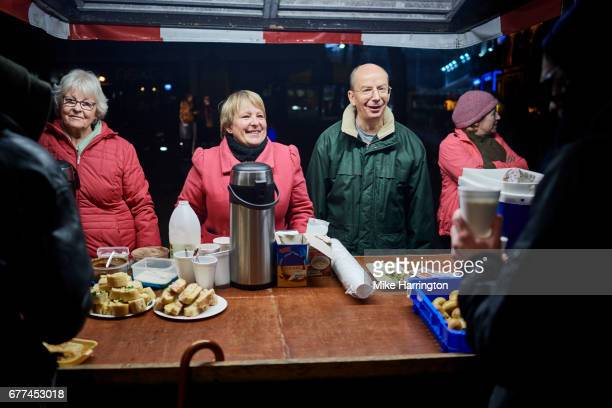 four mature volunteers working at local outdoor soup kitchen - homelessness stock pictures, royalty-free photos & images