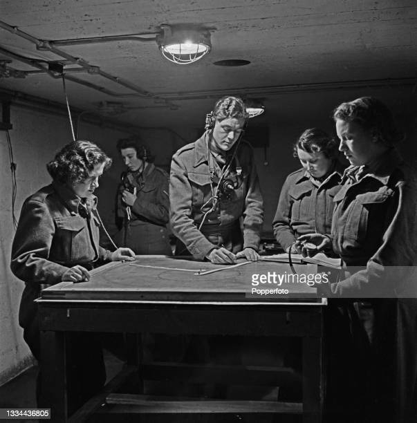 Four members of the British Army Auxiliary Territorial Service plot the course of enemy aircraft on a map in the operations room of an Anti Aircraft...