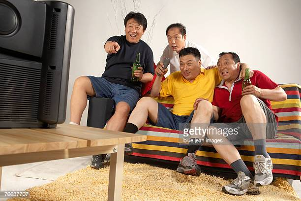 Four men are watching TV.