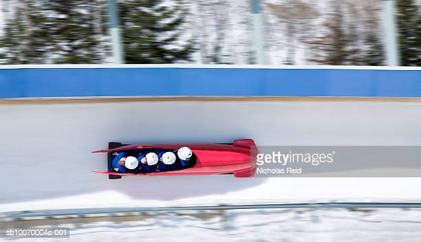 Four men bobsled racing down track, view from above (blurred motion)