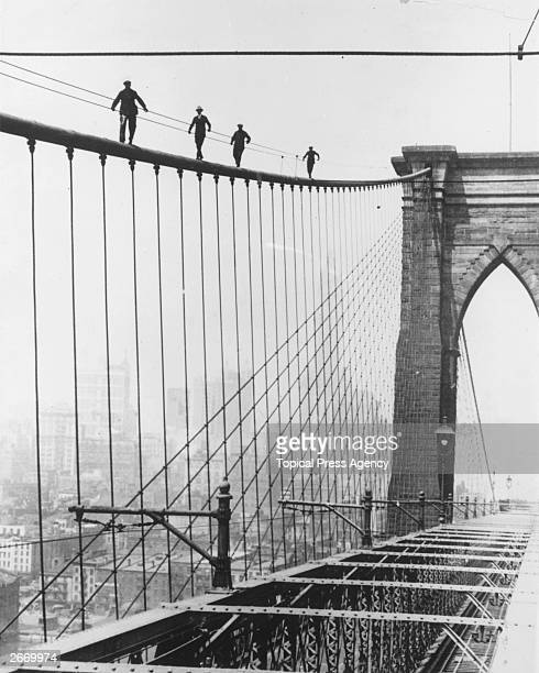 Four men climbing Brooklyn Bridge in New York City as part of a test for applicants wishing to be appointed to paint the bridge