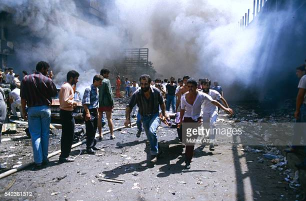 Four men desperately running with a stretcher bearing a wounded victim of a car bomb explosion in the Muslim quarter of Beirut, while in the...
