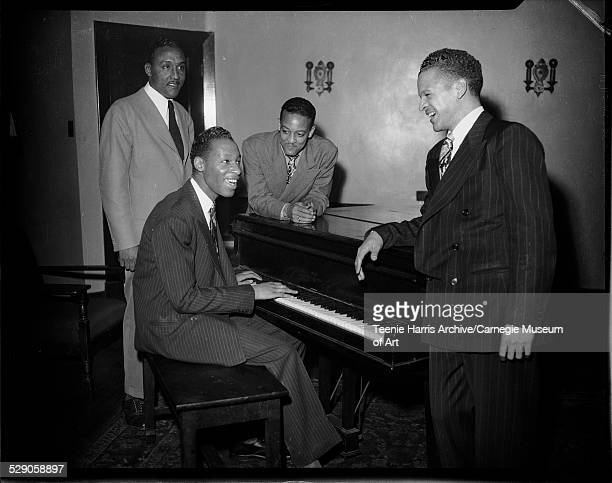 Four men including George Thompson on left and Warren Watson on right leaning against piano in Loendi Club Pittsburgh Pennsylvania circa 19401958