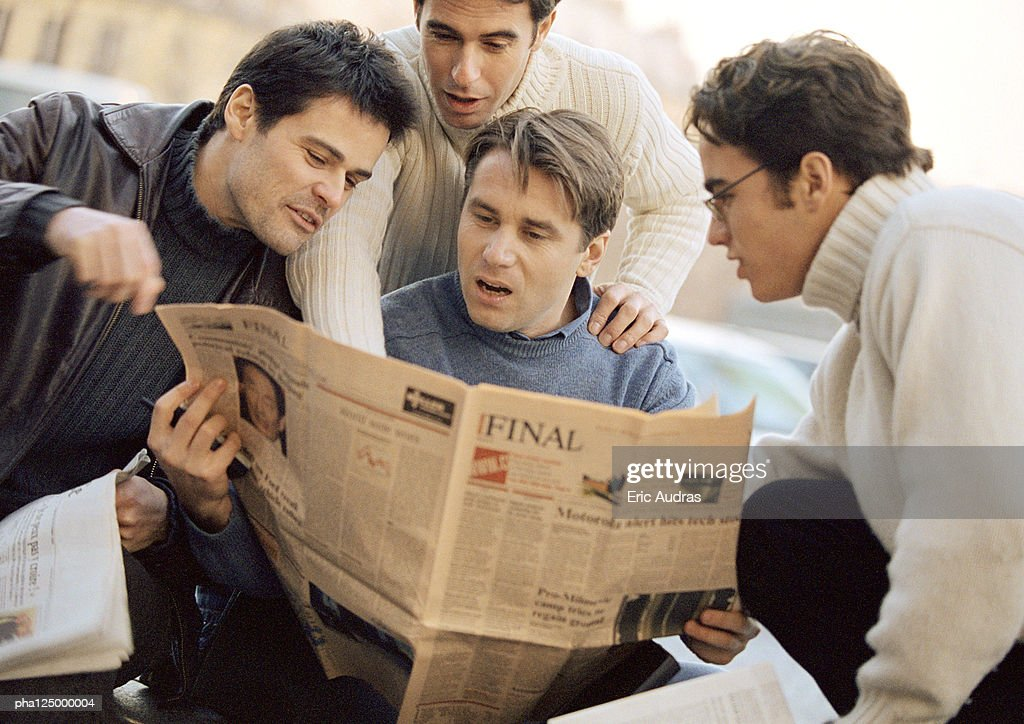 Four men looking at newspaper : Stockfoto