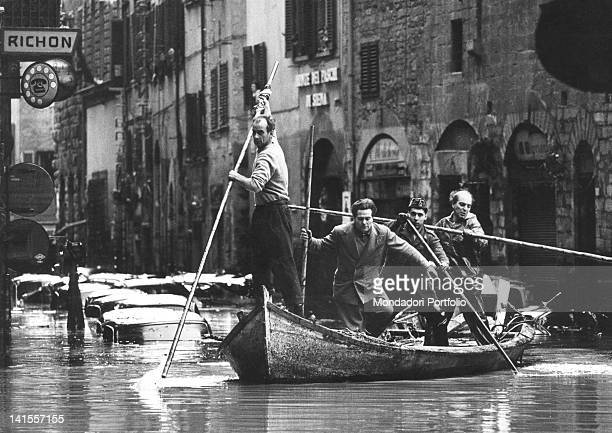 Four men moving by boat along a flooded street of Florence Florence November 1966