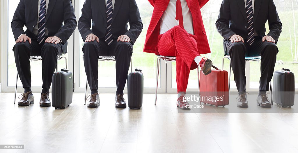 Four men on chairs, three black one red suit : Foto stock