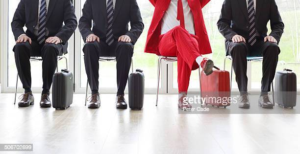 four men on chairs, three black one red suit - individualität stock-fotos und bilder